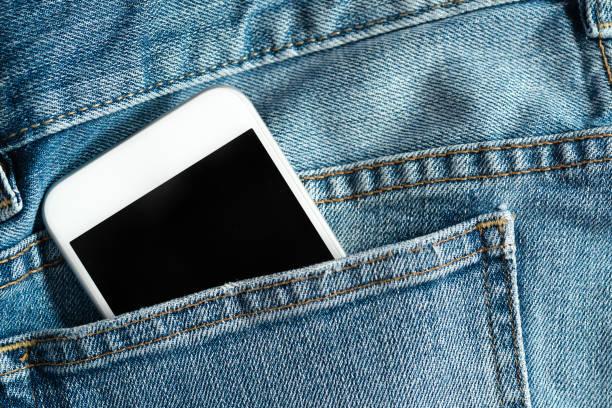 Close up of smartphone in back pocket on pants - foto de acervo