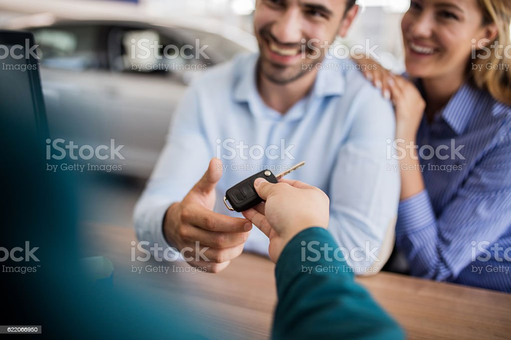 Close up of smiling couple receiving new car key. – Foto
