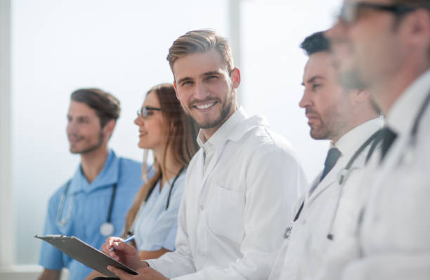 Close up of smiling doctor sitting with his team stock photo