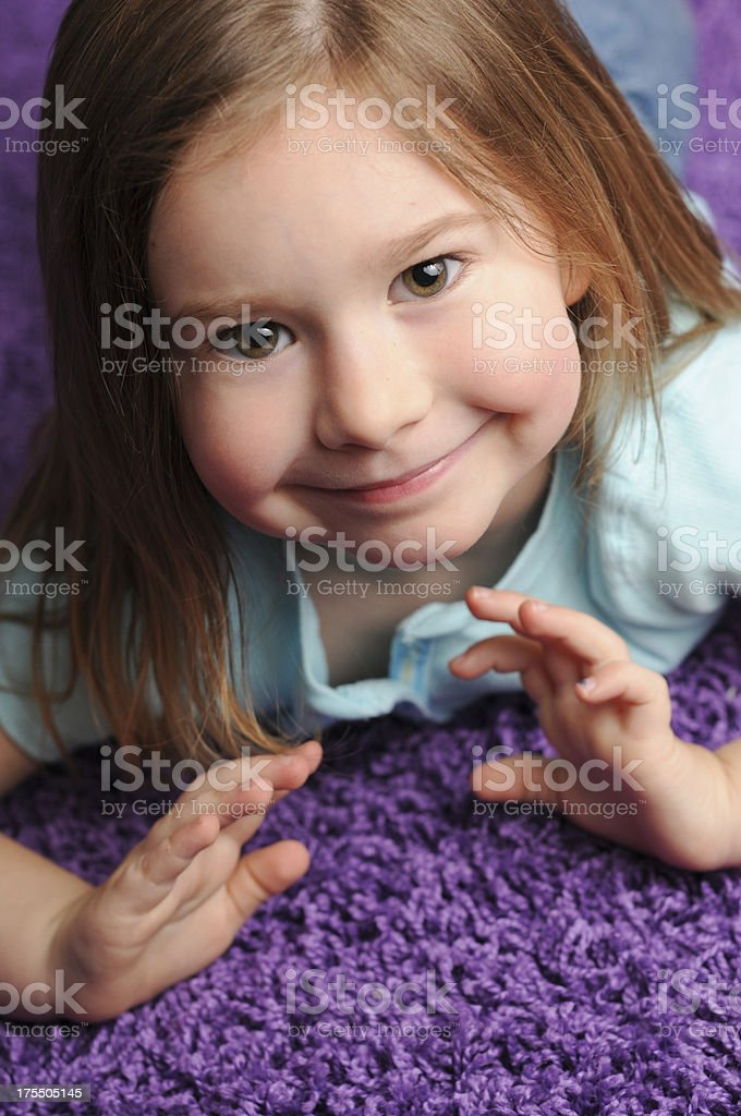 close up of smiling little girl lying on purple carpet stock photo