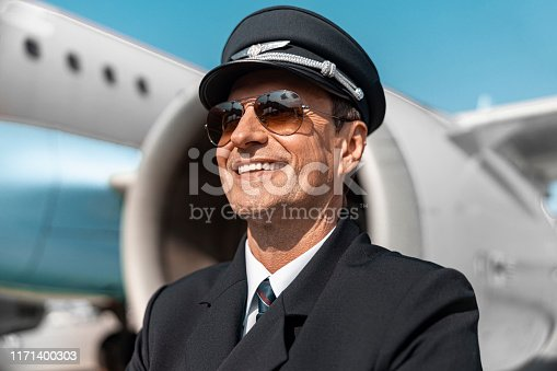 Nice landing. Caucasian adult pilot in cap standing near airplane stock photo