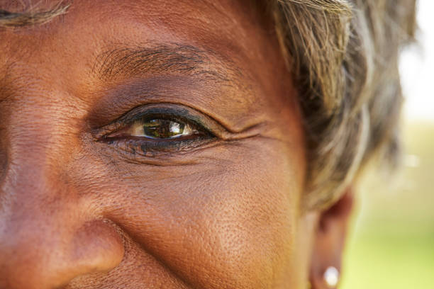 Close Up Of Smiling Senior Womans Eyes In Park stock photo