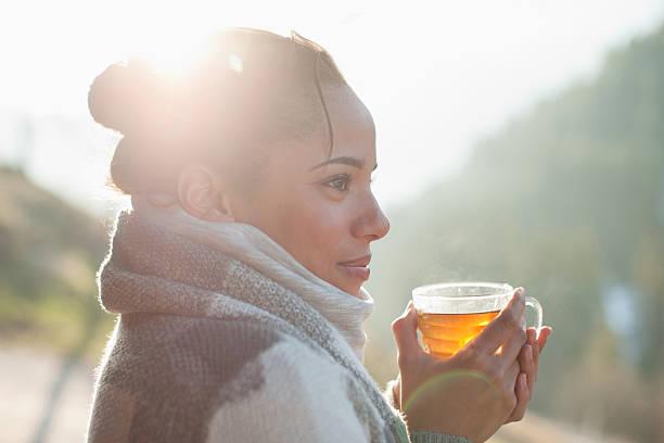 nahaufnahme von lächelnden frau trinkt tee im freien - kalte sonne stock-fotos und bilder