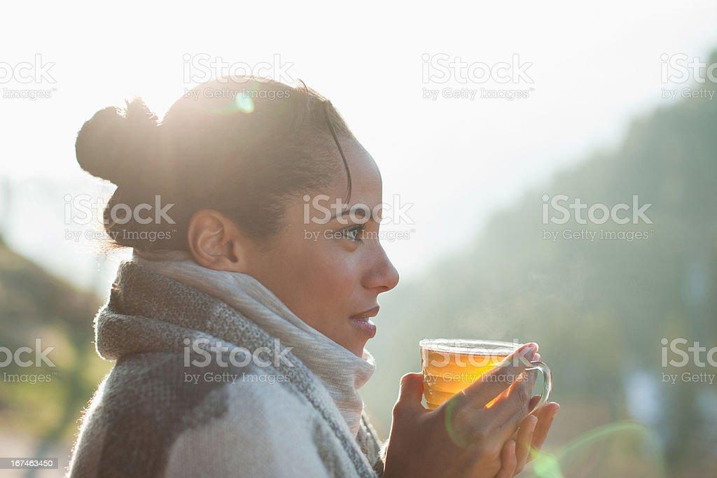 Primer plano de mujer sonriente bebiendo té al aire libre - foto de stock
