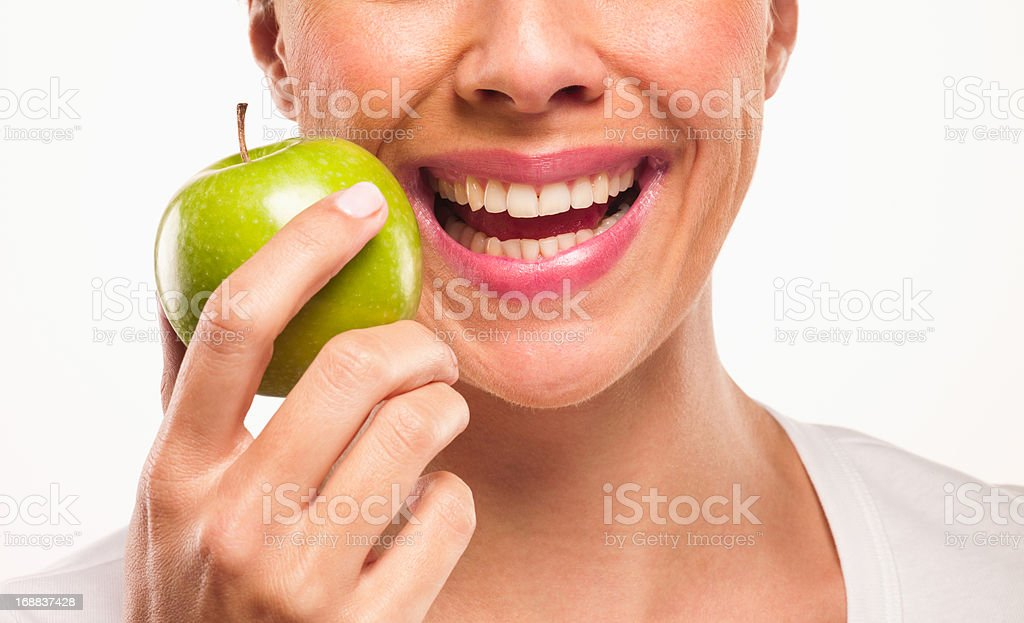Close up of smiling woman holding green apple stock photo