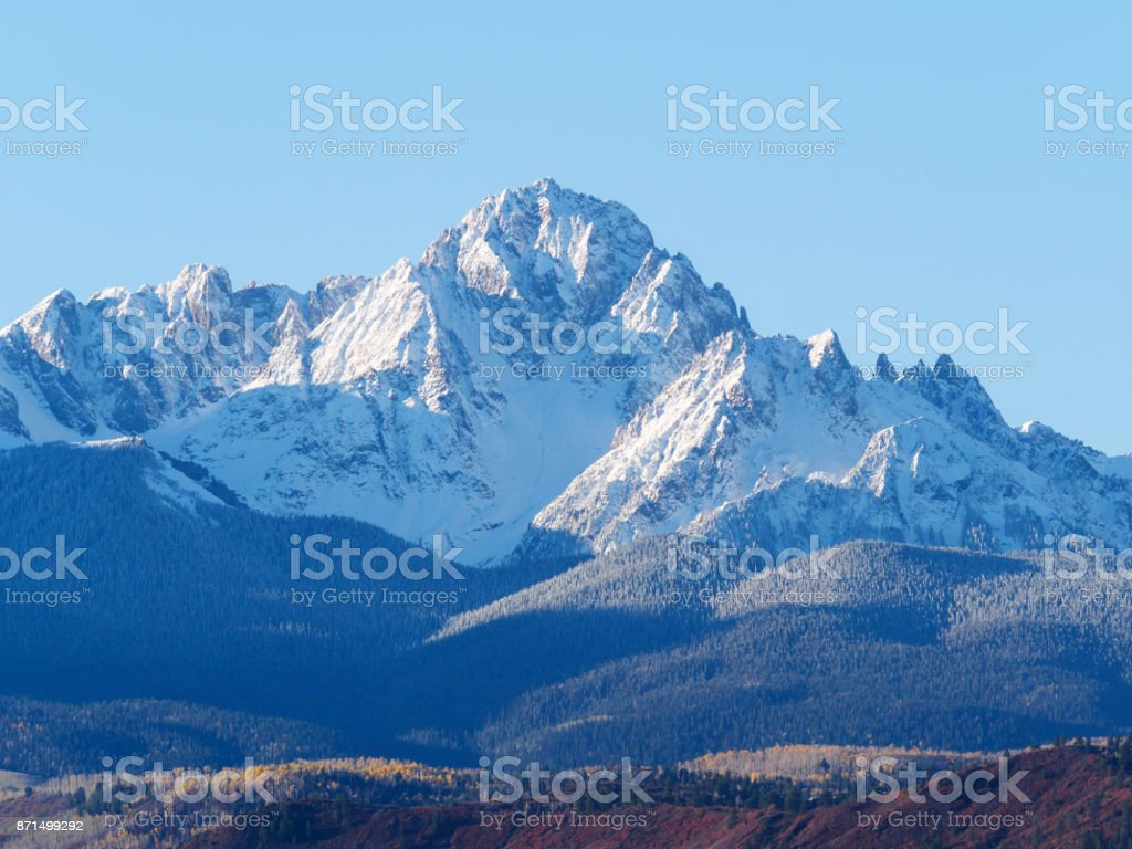 Close up of snow covered Sneffels Range in a bright daylight blue sky in fall foliage autumn season near Ridgway, Colorado, USA. stock photo