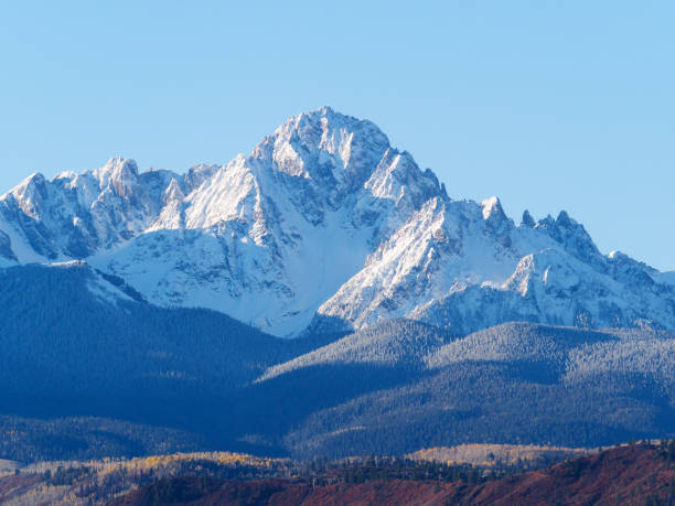 Close up of snow covered Sneffels Range in a bright daylight blue sky in fall foliage autumn season near Ridgway, Colorado, USA. Close up of snow covered Sneffels Range in a bright daylight blue sky in fall foliage autumn season near Ridgway, Colorado, USA. san juan mountains stock pictures, royalty-free photos & images