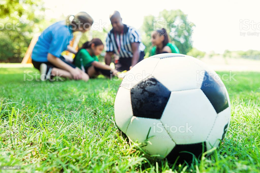 Close up of soccer ball wilth injured player in background stock photo