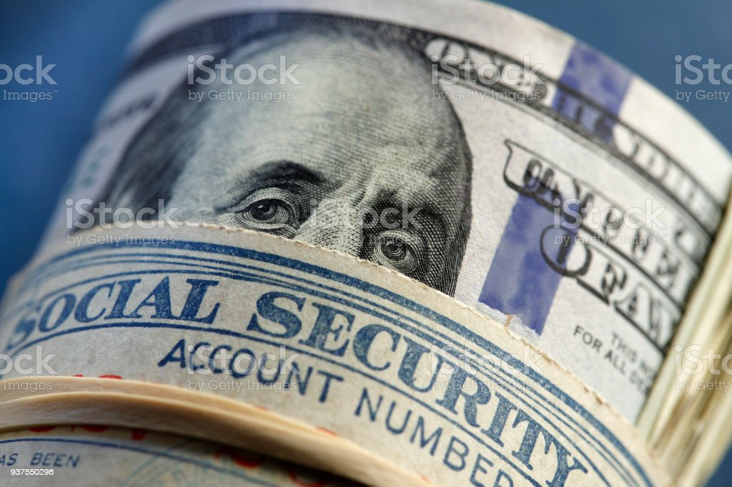 Close Up Of Social Security Card Rolled Up With Money Roll stock photo