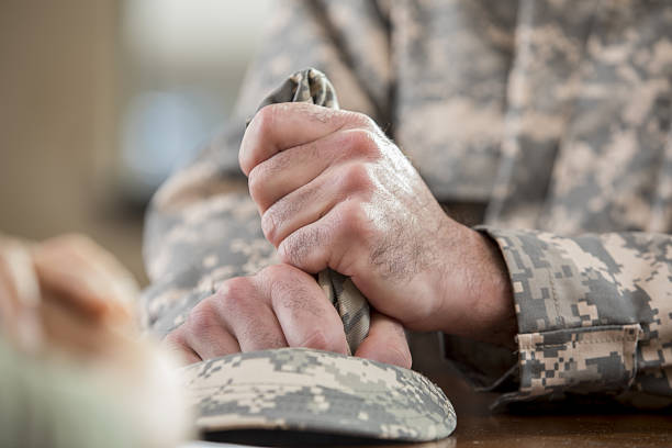 Close up of soldier's hands holding hat in counseling session Caucasian male veteran squeezes camouflage uniform hat during counseling session. Close up is of the man holding the hat. post traumatic stress disorder stock pictures, royalty-free photos & images