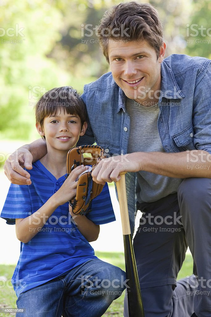 Close up of son and his dad holding baseball equipment stock photo