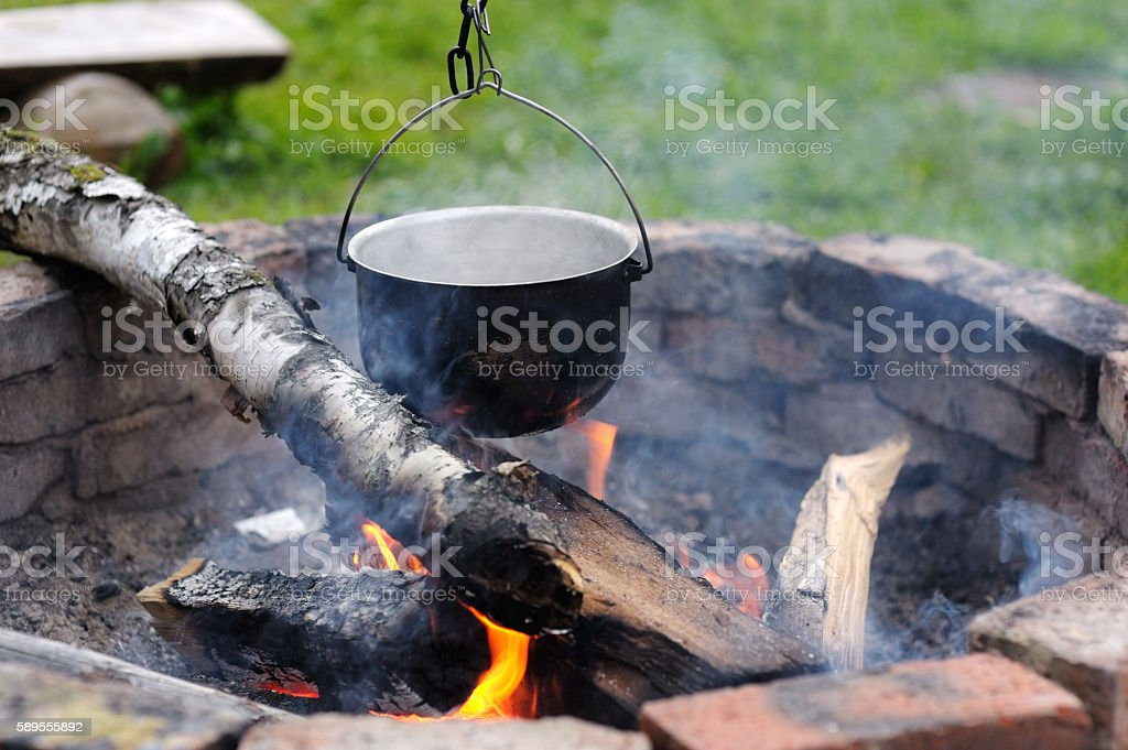 Close up of soup cooking over campfire. Travel. stock photo