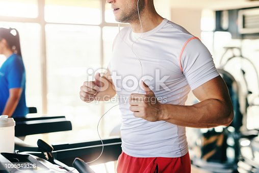 istock Close up of sporty Caucasian man in sportswear running on the treadmill in the gym. Earphones in the ears. 1095349326