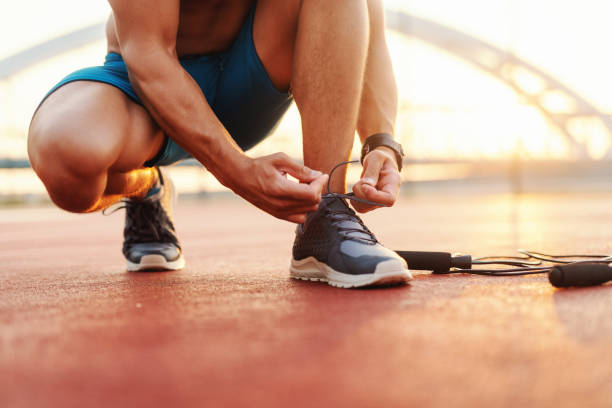 Close up of sporty man tying shoelace while kneeling in a court in the morning. Next to him skipping rope. stock photo