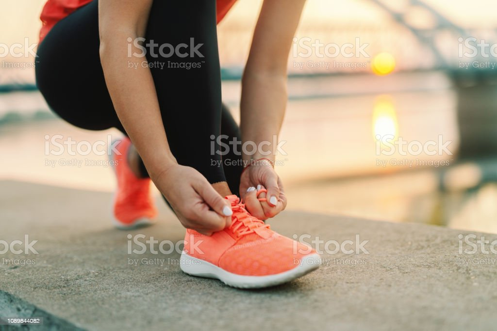 Close up of sporty woman tying shoelace while kneeling outdoor, In background bridge. Fitness outdoors concept. - Foto stock royalty-free di Abbigliamento
