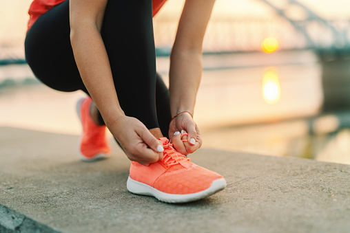 Close Up Of Sporty Woman Tying Shoelace While Kneeling Outdoor In Background Bridge Fitness Outdoors Concept - Fotografie stock e altre immagini di Abbigliamento