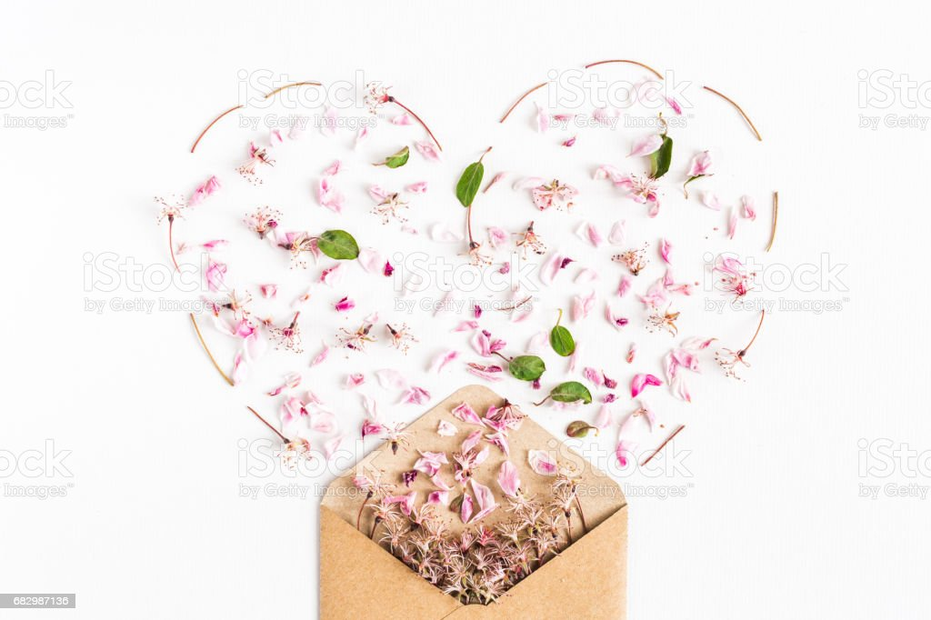 close up of spring flowers flowers spilled from an envelope in the form of heart on white background. top view. concept of love and proposal. Flat lay foto de stock royalty-free