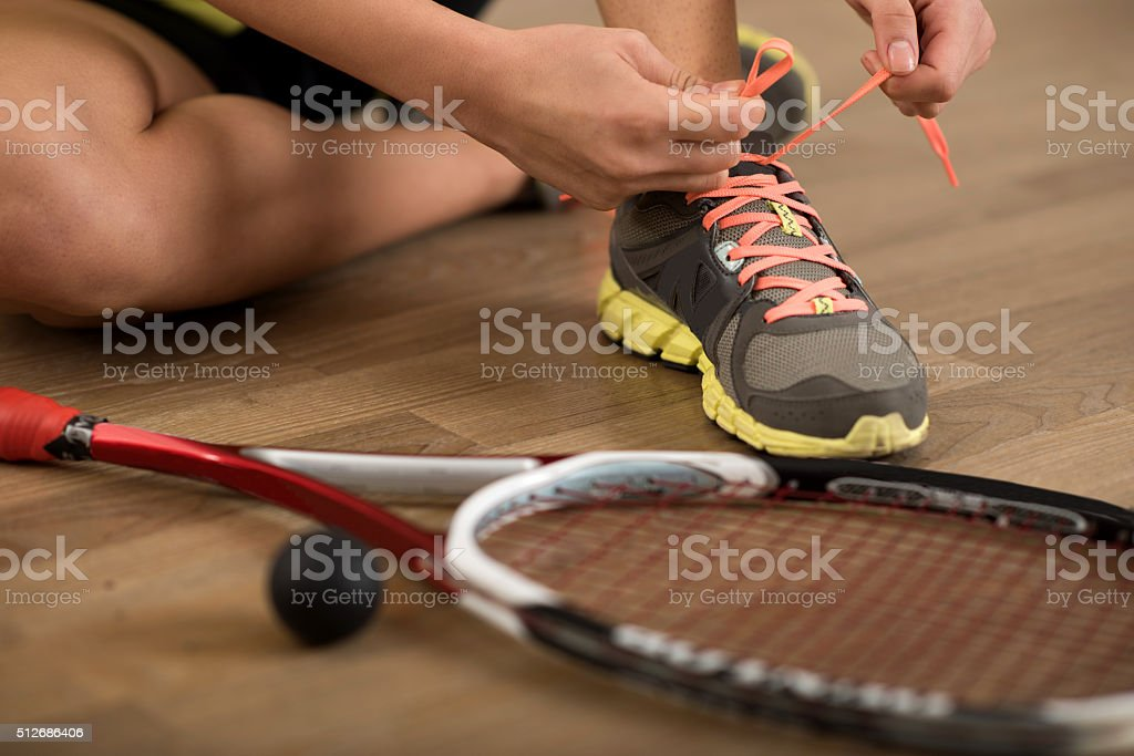 Close up of squash player tying shoelaces on sports sneakers. stock photo