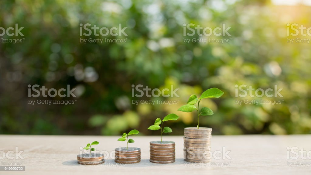 Close up of stacking coins with green bokeh background stock photo