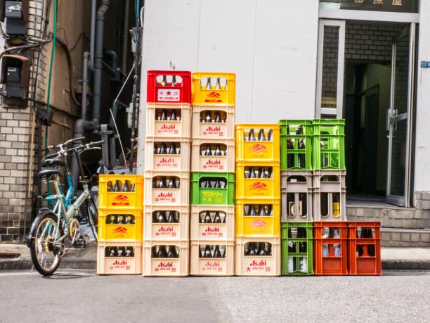 eine nahaufnahme von stapel von kunststoff rot, weiß und gelb kisten mit asahi bier und alkoholfreie getränke flaschen in japan. - dokumentation stock-fotos und bilder