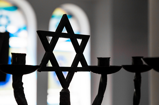 Close up image depicting the Jewish religious symbol of the star of David inside a synagogue. The star is in silhouette, while in the background stained glass windows are blurred out of focus. Horizontal colour image with copy space.