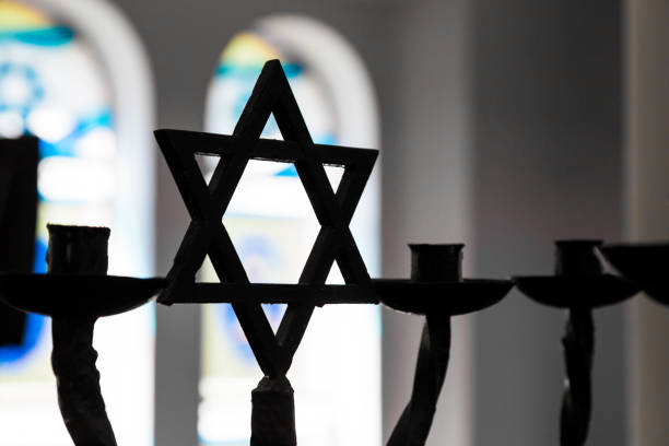 Close up of Star of David silhouette inside Jewish Synagogue Close up image depicting the Jewish religious symbol of the star of David inside a synagogue. The star is in silhouette, while in the background stained glass windows are blurred out of focus. Horizontal colour image with copy space. judaism stock pictures, royalty-free photos & images