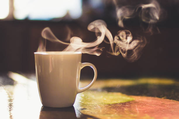 Close up of steaming cup of coffee or tea on vintage table - early morning breakfast on rustic background Cup of hot drink on the table caffeine stock pictures, royalty-free photos & images