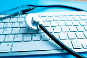 istock Close up of stethoscope on computer keyboard. Health concept 1215888810