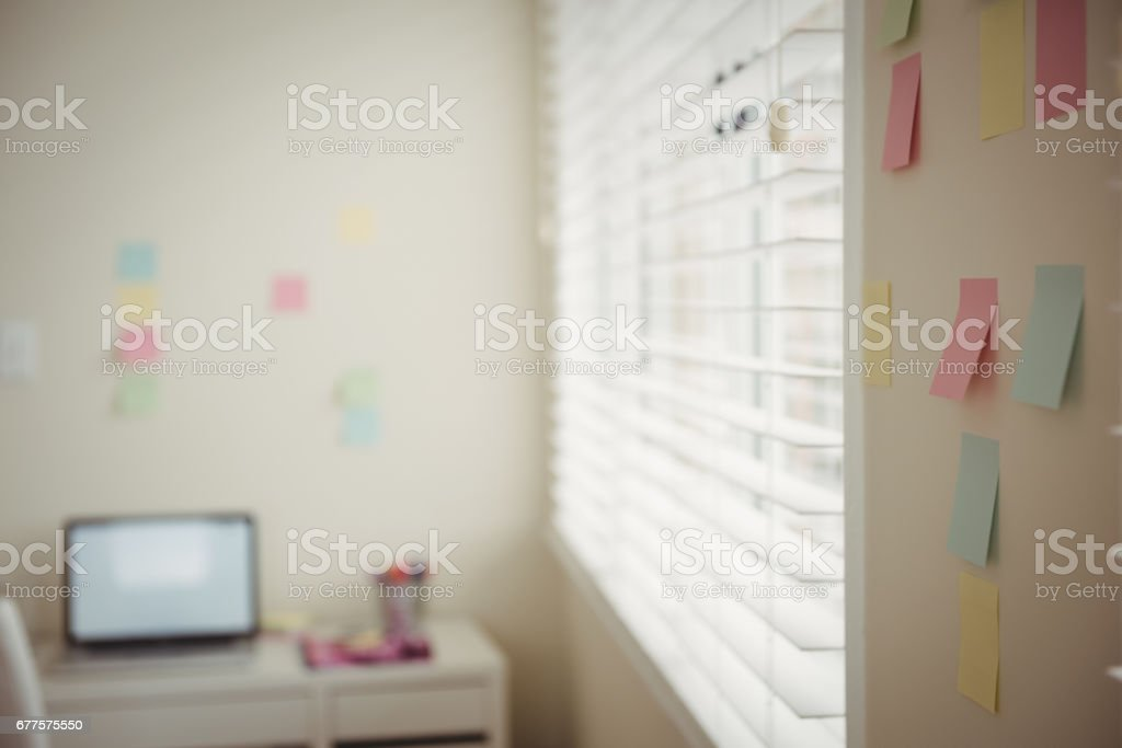 Close up of sticky notes on wall by laptop on table royalty-free stock photo