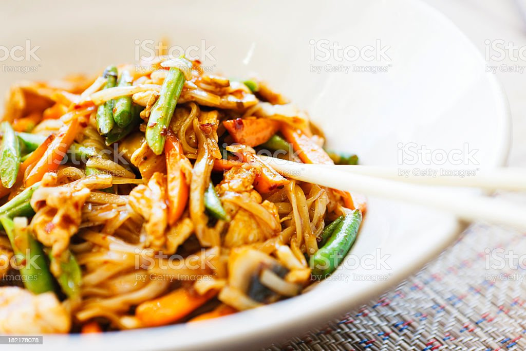 Close up of stir-fried Thai chicken in bowl plus chopsticks stock photo