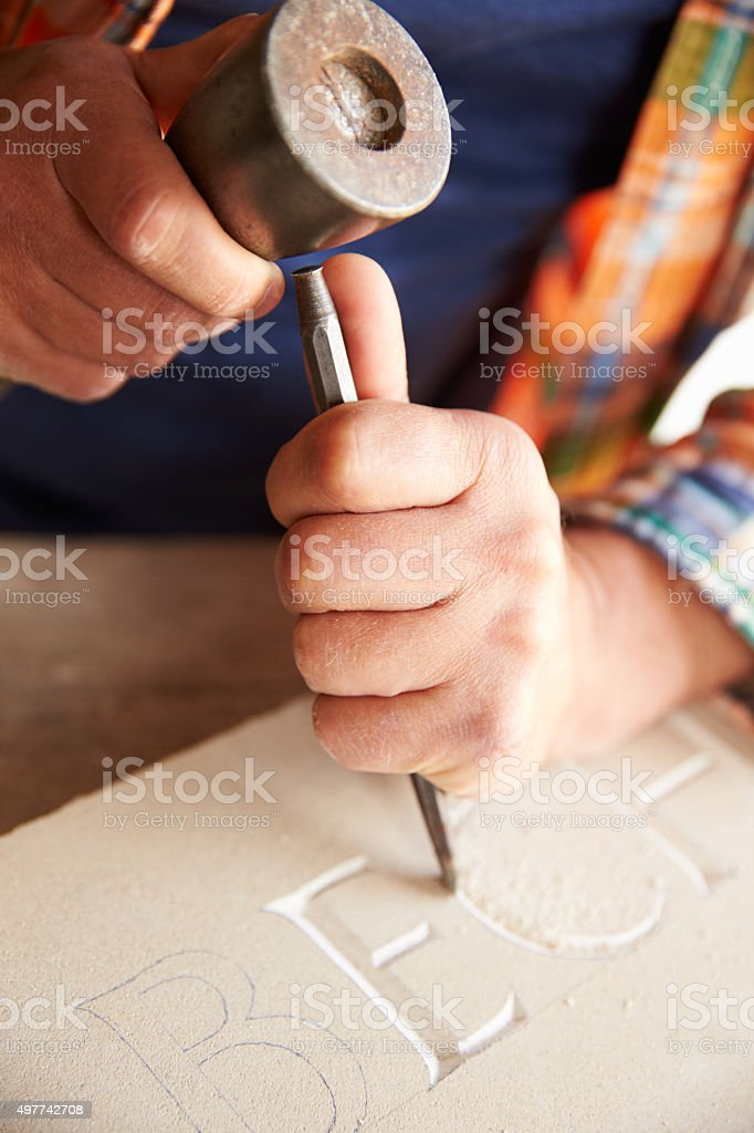 Close Up Of Stone Mason Working On Carving In Studio stock photo