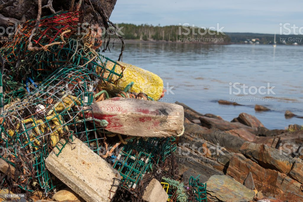 A close up of storm damaged lobster traps on a rocky shore line. stock photo