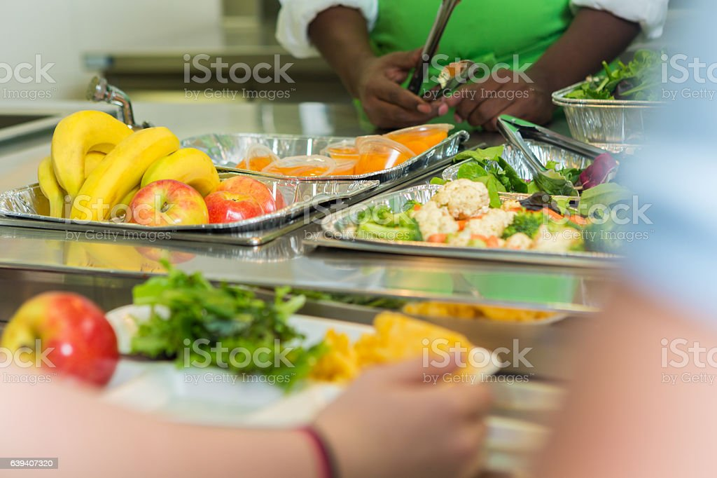 Close up of students being served in high school cafeteria stock photo