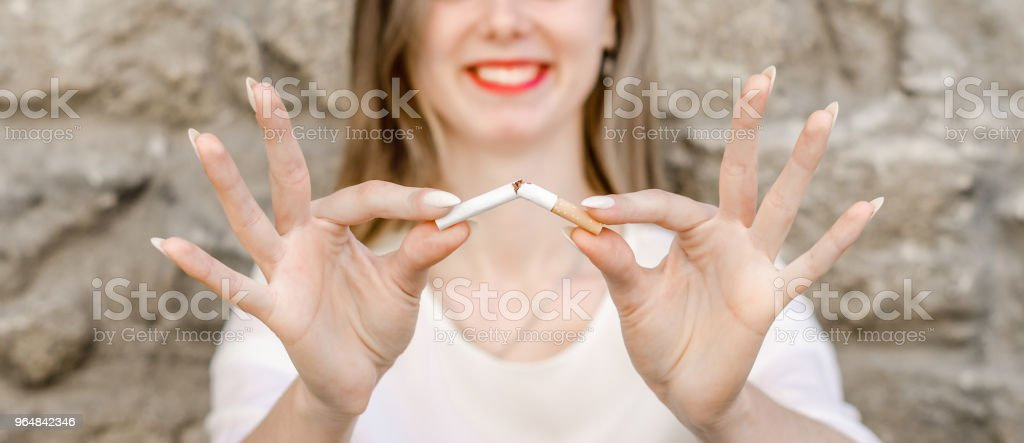 Close Up Of Stylish Smiling Woman Smoking Cigarette Outdoor Denim Shirt in park on Nature Background Habit Prohibited Advertising royalty-free stock photo