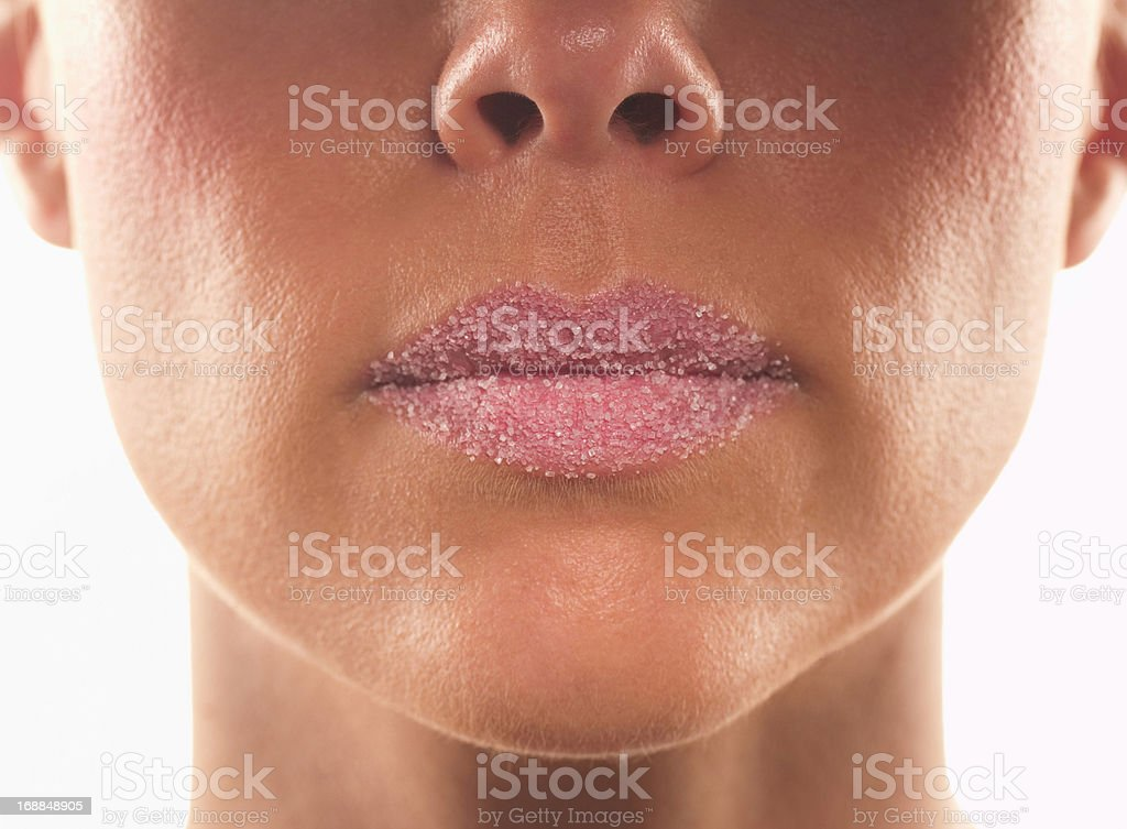 Close up of sugar covering lips of woman with pink lipstick royalty-free stock photo