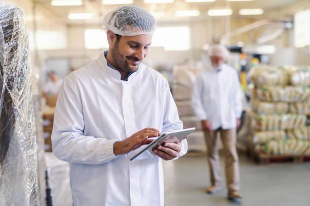 närbild av handledare i uniform med surfplatta för att kontrollera data när du står i matfabriken. - livsmedelstillverkningsfabrik bildbanksfoton och bilder