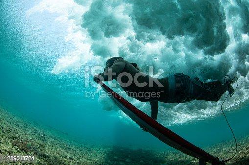 A close up shot of a local Maldivian surfer duck diving under a wave