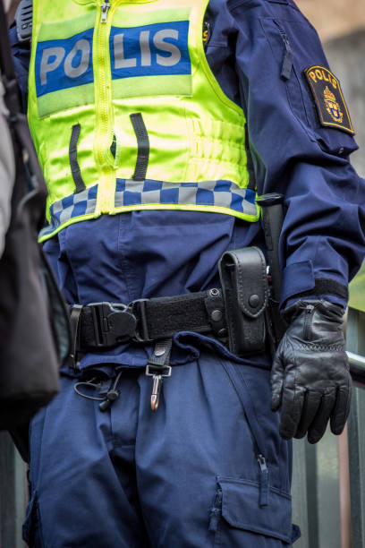 Close up of Swedish police officer wearing a luminous yellow green vest with police text and belt with equipment. stock photo