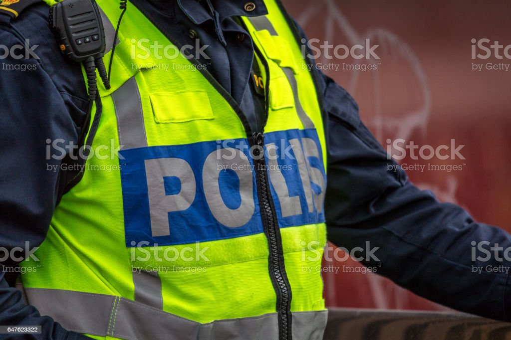 Close up of Swedish police officer wearing a luminous yellow green vest with police text. stock photo