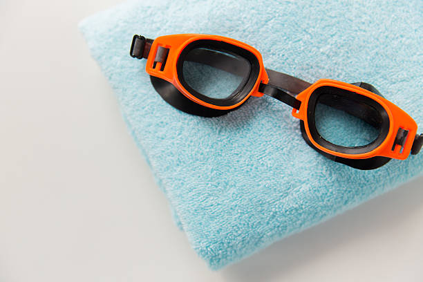 close up of swimming goggles and towel sport, fitness, water sports and objects concept - close up of swimming goggles and towel swimming goggles stock pictures, royalty-free photos & images