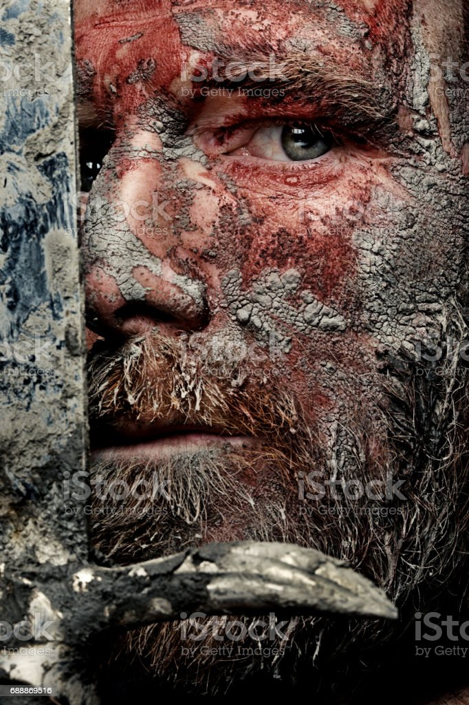 Close up of sword wielding dirty and bloody viking warrior in studio shot stock photo