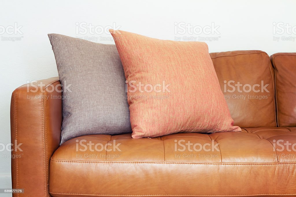 Close up of tan leather sofa with linen cushions stock photo
