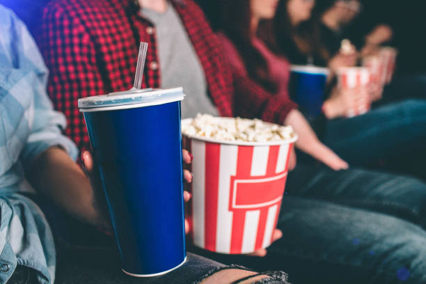 close up of tasty but unhealthy food. there are basket of popcorn and a blue cup of coke on picture. man and woman are holding it together. - film industry stock pictures, royalty-free photos & images