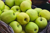 Close up of tasty green apples in a wicker basket for sale at a farmer's market