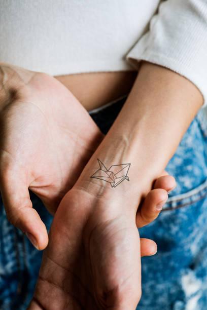 tattoo am handgelenk einer frau hautnah - tattoos frauen arm stock-fotos und bilder