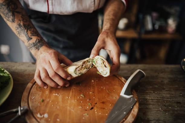 nahaufnahme von tätowierten koch hände halten einen wrap-sandwich - essen tattoos stock-fotos und bilder