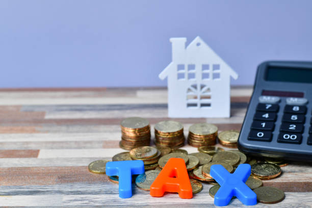 Close up of TAX word on wooden home and stack money coins stock photo