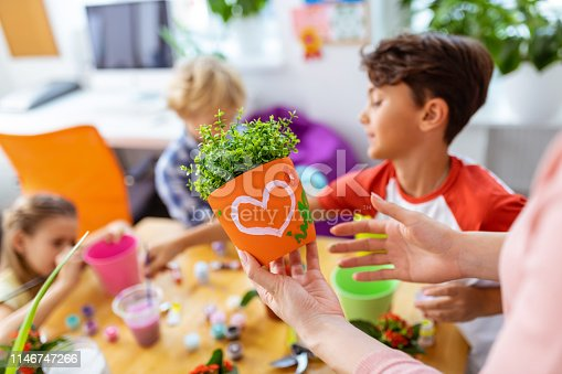 Flowerpot with picture. Close up of teacher holding orange flowerpot with nice picture while standing near pupils