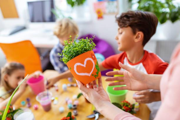 Nahaufnahme des Lehrers mit orangefarbenem Blumentopf mit schönem Bild – Foto