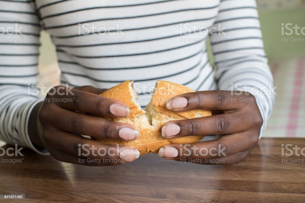 Close Up Of Teenage Girl Breaking Open Bread Roll stock photo